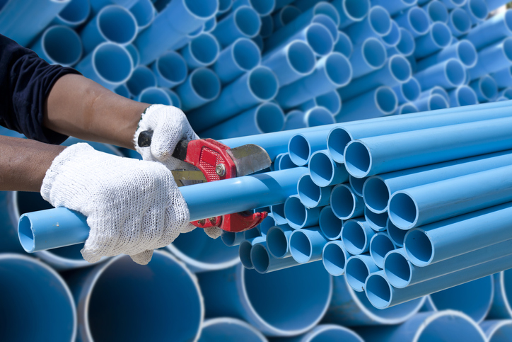 Worker cuting blue pvc pipe in construction site.